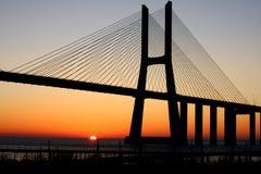Sunrise at Lisbon. Vasco da Gama bridge, backlit by a mid June sunrise, at Lisbon, Portugal. Image unsharpened stock images