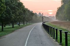 Sunrise London Hyde Park. Sunrise in London Hyde Park on foggy morning with trees growing on both sides of park lane and orange sky in the distance Royalty Free Stock Photos