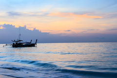 Sunrise and long tail boat on the ocean waves Royalty Free Stock Photos