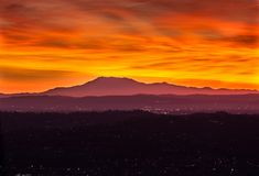 Sunrise at the Los Angeles basin, looking east. Colorful sunrise as seen from Griffith Park, Los Angeles, California. Orange and red, above purple mountains stock photography