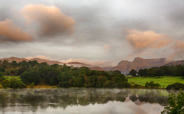 Sunrise at Loughrigg Tarn in Lake District. Sun rising and illuminating Langdale Pikes with Loughrigg Tarn in foreground Royalty Free Stock Images