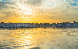 The sunrise in Luxor. LUXOR, EGYPT - OCTOBER 8, 2014: The bright sky reflects in the Nile waters during the sunrise, on October 8 in Luxor, Egypt stock photos