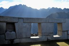 Sunrise through Machu Picchu windows. The sun rises over steep mountains and shines through rock windows of ruins at Machu Picchu in Peru Royalty Free Stock Photos