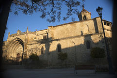 Sunrise in main facade on Church of San Pablo framed by a few branches with blue sky, Ubeda