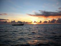 Sunrise at maldives. Maldives sunrise at 5.54 a.m. with a little boat Stock Image