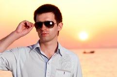 Sunrise man. Man is holding sunglasses at sunrise near sea Stock Photos
