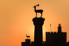 Sunrise in Mandraki harbor. Rhodes, Greece. Medieval statue of deer where the Colossus of Rhodes may have stood, Greece Royalty Free Stock Photography