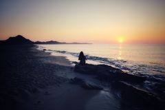 Sunrise Meditation. Woman meditating on a beach at sunrise royalty free stock photography