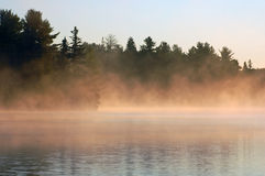 Sunrise and mist. In beautiful lake in Algonquin Park Stock Photo