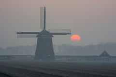 Sunrise misty winter morning with windmill Stock Image