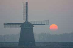 Sunrise misty winter morning with windmill Royalty Free Stock Image