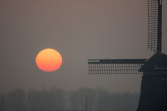 Sunrise misty winter morning with windmill Stock Images