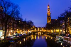 Morning blue sunrise on Amsterdam canal with Church bell tower on the background horizon stock photo