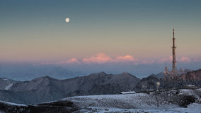 Sunrise, moon set. Red peak with moon on the top of a mountain Royalty Free Stock Photos