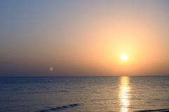 Sunrise, moonset. Rising Sun and sitting Moon over the sea Royalty Free Stock Photo