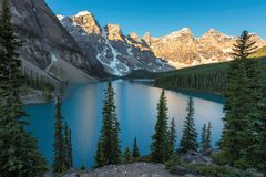 Sunrise at Moraine lake in Banff National Park, Canada. Beautiful sunrise under turquoise waters of the Moraine lake with snow-covered peaks above it in Stock Photos