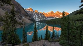 Sunrise at Moraine lake in Canadian Rockies, Banff National Park, Canada. Beautiful sunrise under turquoise waters of the Moraine lake with snow-covered peaks stock photography