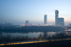 Sunrise at Moscow. Sunrise in Moscow. Several modern buildings under construction and passing train at bottom of the image. Also heavy smog from fire at the city Stock Photos