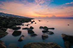 Sunrise at mossy rock near ocean with milky looking water Stock Photography