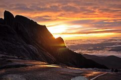 Sunrise at Mount Kinabalu. The sky takes on shades of orange during sunrise, the colour that gives you hope that the sun will set only to rise again Stock Photo