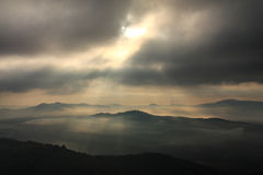 Sunrise on the mount. Sky is closed by the clouds but the light of the sun still shine through thems Royalty Free Stock Photography