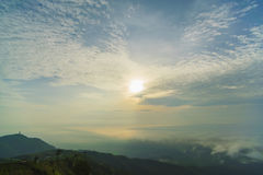 Sunrise at mountain with fog and clouds in the blue sky.  Royalty Free Stock Photos