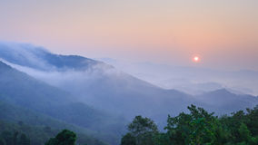 Sunrise, mountain and fog in the morning Stock Images