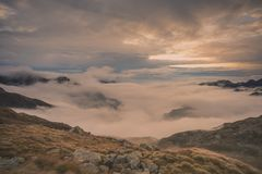 Mountain landscape sunrise lights. Mountain valley covered with clouds in early morning,you can see the summits of the tall mountain peaks, ticking above the royalty free stock image