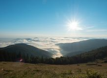 Sunrise in mountain pasture at summer. Carpathians mountains, west Ukraine. Low white clouds flowing between ranges. Rising sun in blue sky. Ukrainian nature stock photos