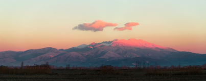 Sunrise in the mountain. A mountain ranges is colored by the first morning sun light Stock Photography