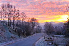 Sunrise and mountain village road Stock Photography