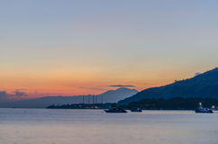 Sunrise with mountains and boats. At the sea stock photos