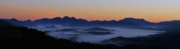 Sunrise between mountains and fog. Stock Images