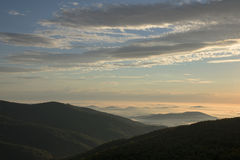Sunrise in the mountains with fog in the valley Stock Images