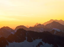 Sunrise in Mountains. Sunrise from Kriváň hill in High Tatras mountain in Slovakia. Orange light floods cascade of hills royalty free stock photo