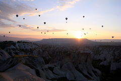 The sunrise in the mountains with a lot of air hot balloons in the sky. Stock Photography