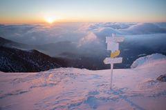 Sunrise in mountains, orientation signs in foreground Stock Images