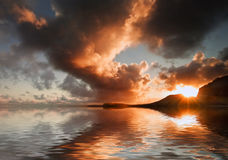 Sunrise and mountains refelcted in sea Royalty Free Stock Images