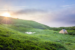 Sunrise in mountains with a tourist tent and a little lake in vi Royalty Free Stock Images
