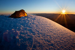 Sunrise in the mountains. Yellow tent on the summit at a sunrise Royalty Free Stock Image