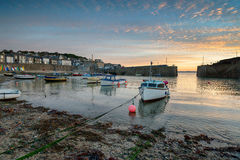 Sunrise at Mousehole. Sunrise over boats in the harbour at Mousehole on the Cornish coast Stock Image