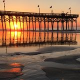 Sunrise at Myrtle Beach. The sun rises behind the second Avenue Pier in Myrtle Beach South Carolina Stock Photos