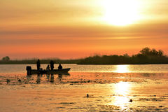 Sunrise in nature reservation of Danube delta, Romania. Tourist on boats looking to sunrise in nature reservation of Danube delta, Romania royalty free stock photography