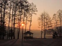 Sunrise near lake. Arbor, trees  and lake in sunrise colors, Lithuania Stock Photo