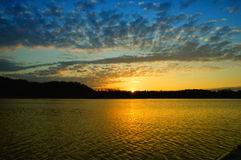 Sunrise with nice clouds. Golden sunrise with streaming clouds over a blue sky. on the lake with gold reflections as the sun rises over the woods Royalty Free Stock Photo