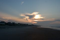 Sunrise in North Carolina's Outer Banks. A dramatic sunrise on the beach of Emerald Isle, North Carolina.  A strong beam of sunlight shoots from behind the cloud Royalty Free Stock Image
