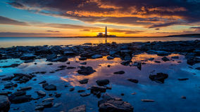 Sunrise on the Northumberland coast, England. St.Mary's lighthouse sits on the Northumberland coast, early morning sunrise capturing the reflection of the sky Stock Photos