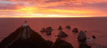 Sunrise on Nugget Point with Lighthouse. Gorgeous colorful lighthouse at sunrise on Nugget Point, South Island, New Zealand stock images