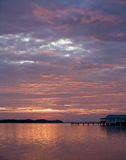 Sunrise in Oak Hill Florida. Dock fish camp orange sky with lavender and purple clouds and reflections Stock Photography