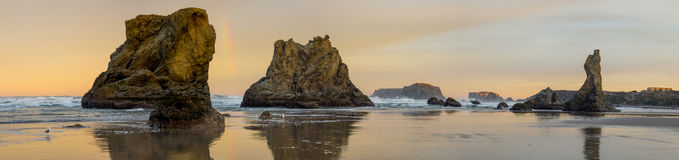 Sunrise on ocean beach with cliffs. A colorful sunrise at the sandy beach with rocky cliffs and stacks at Bandon, Oregon on the Pacific Ocean Stock Photography